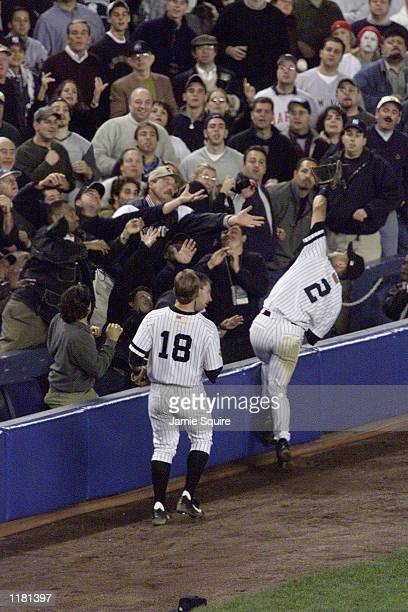 Derek Jeter of the New York Yankees makes a catch in the stands during Game five of the American League Divisional Championship against the Oakland...