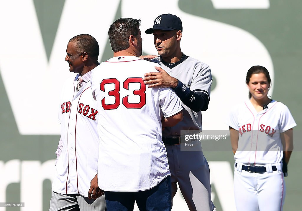 Derek Jeter #2 of the New York Yankees meets former Red Sox captain Jason Varitek as he is honored prior to the last game of the season against the Boston Red Sox at Fenway Park on September 28, 2014 in Boston, Massachusetts.