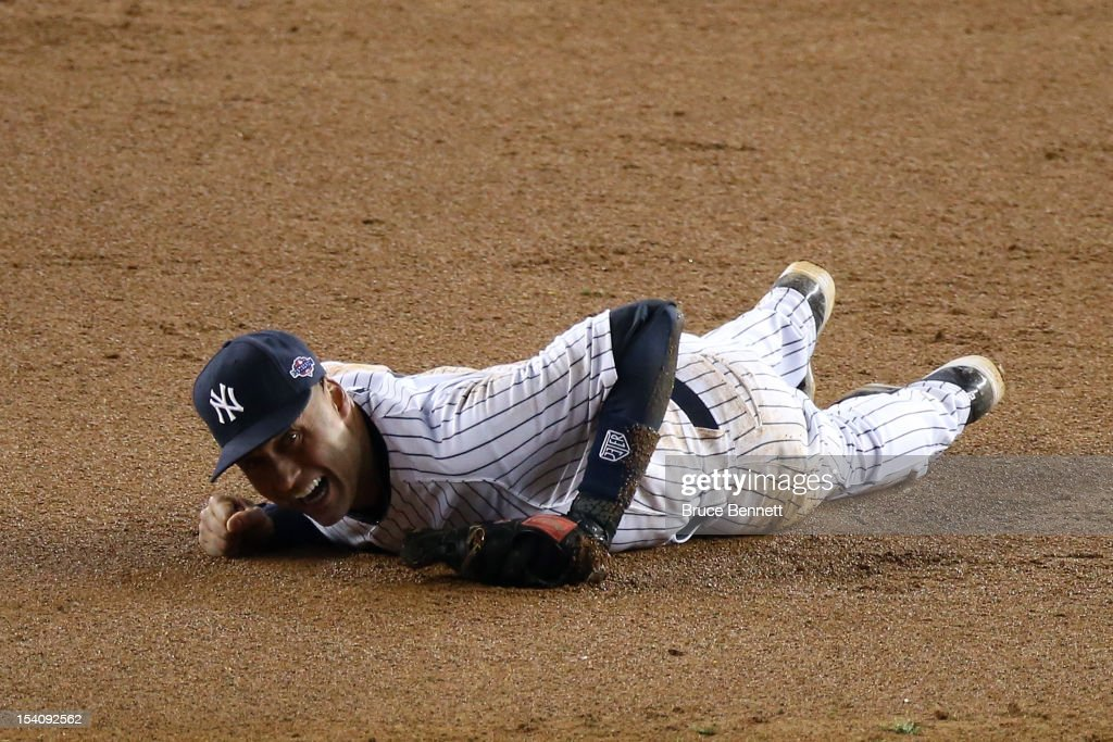 Derek Jeter #2 of the New York Yankees reacts after he injured his leg in the top of the 12th inning against the Detroit Tigers during Game One of the American League Championship Series at Yankee Stadium on October 13, 2012 in the Bronx borough of New York City, New York.