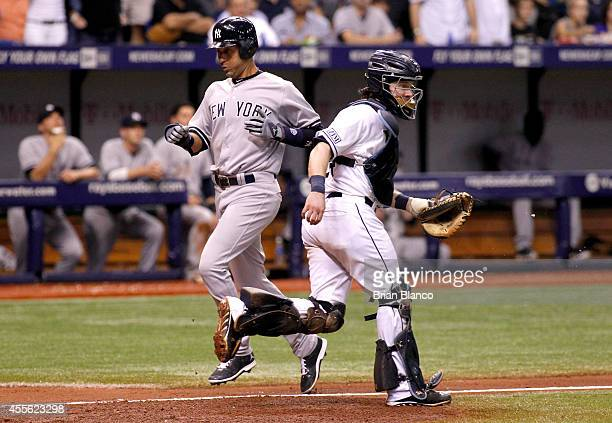 Derek Jeter of the New York Yankees scores in front of catcher Ryan Hanigan of the Tampa Bay Rays on a sacrifice fly by Brett Gardner in the sixth...