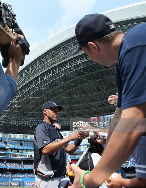 Derek Jeter of the New York Yankees signs autographs for fans before the start of MLB game action against the Toronto Blue Jays on August 31 2014 at...