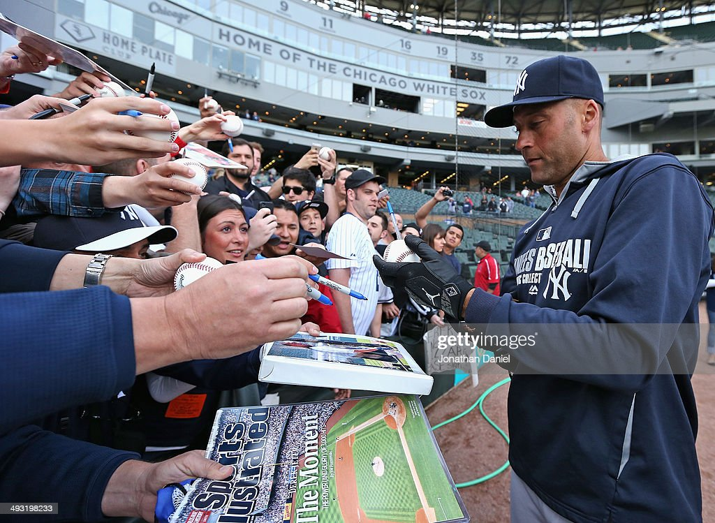 Derek Jeter of the New York Yankees signs autographs for fans before a game against the Chicago White Sox at US Cellular Field on May 22 2014 in...