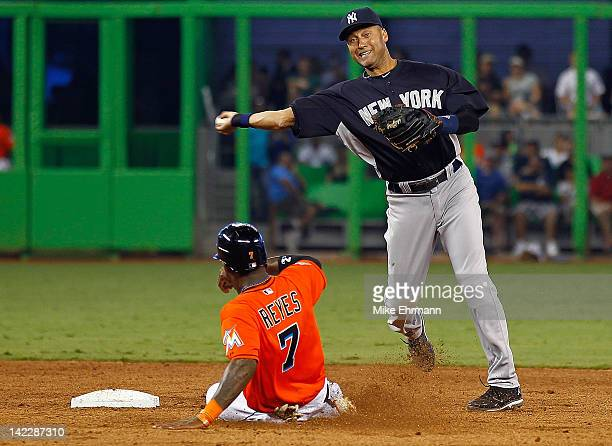 Derek Jeter of the New York Yankees turns a double play as Jose Reyes of the Miami Marlins slides into second during a game at Marlins Park on April...