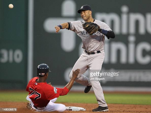 Derek Jeter of the New York Yankees turns a double play as Pedro Ciriaco of the Boston Red Sox slides into second in the third inning during the...