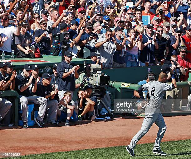 Derek Jeter tips his hat as he is applauded by teammates and fans as he takes he field for the pre game ceremonies The Boston Red Sox hosted the New...