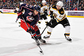 Derek MacKenzie of the Columbus Blue Jackets and Dennis Seidenberg of the Boston Bruins battle for a control of the puck during the first period on...