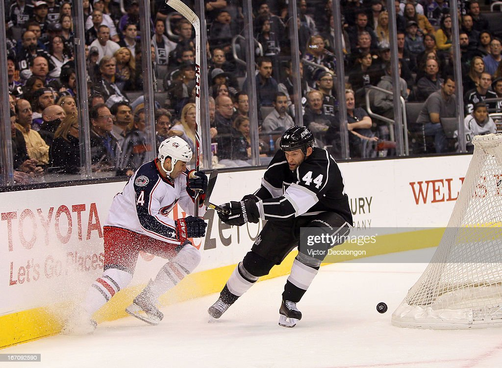 Derek MacKenzie #24 of the Columbus Blue Jackets and Robyn Regehr #44 of the Los Angeles Kings vie for the puck behind the Kings net in the third period of the NHL game at Staples Center on April 18, 2013 in Los Angeles, California. The Kings defeated the Blue Jackets 2-1.