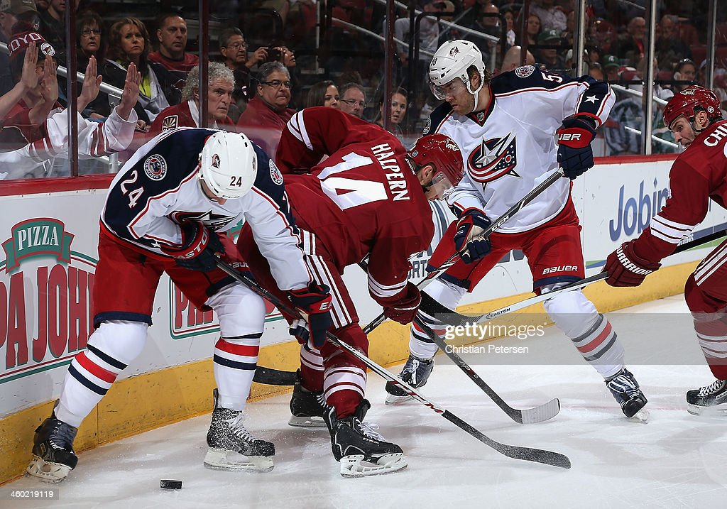 Derek MacKenzie #24 of the Columbus Blue Jackets battles for a loose puck with Jeff Halpern #14 of the Phoenix Coyotes during the first period of the NHL game at Jobing.com Arena on January 2, 2014 in Glendale, Arizona.