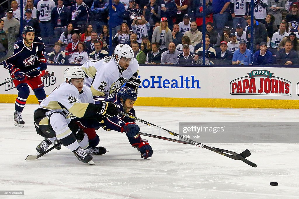 Derek Mackenzie #24 of the Columbus Blue Jackets dives between Olli Maata #3 and <a gi-track='captionPersonalityLinkClicked' href=/galleries/search?phrase=Matt+Niskanen&family=editorial&specificpeople=2106633 ng-click='$event.stopPropagation()'>Matt Niskanen</a> #2, both of the Pittsburgh Penguins to try to get to the puck during the second period of Game Six of the First Round of the 2014 NHL Stanley Cup Playoffs at Nationwide Arena on April 28, 2014 in Columbus, Ohio. Pittsburgh defeated Columbus 4-3 to win the series four games to two.