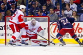 Derek Mackenzie of the Columbus Blue Jackets flips the puck past Jonathan Ericsson of the Detroit Red Wings and Petr Mrazek of the Detroit Red Wings...