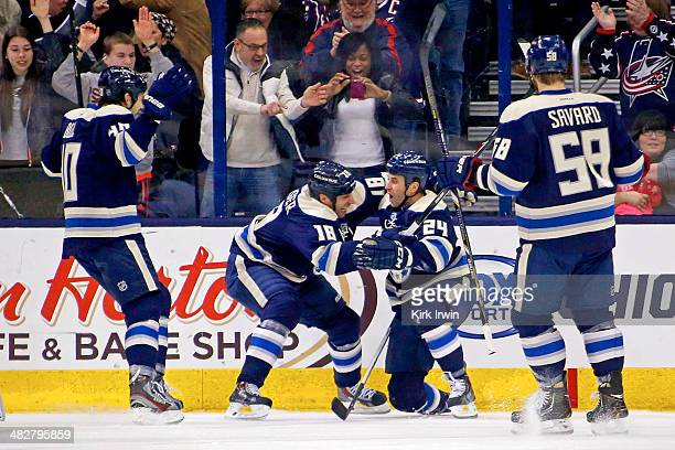 Derek Mackenzie of the Columbus Blue Jackets is congratulated by RJ Umberger Jared Boll and David Savard after scoring a goal against the Chicago...