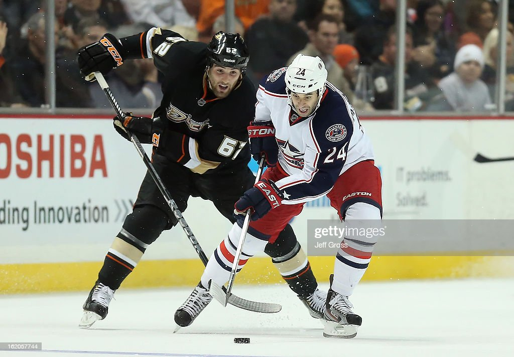 Derek MacKenzie #24 of the Columbus Blue Jackets is pursued by Patrick Maroon #62 of the Anaheim Ducks for the puck in the third period at Honda Center on February 18, 2013 in Anaheim, California. The Ducks defeated the Blue Jackets 3-2.