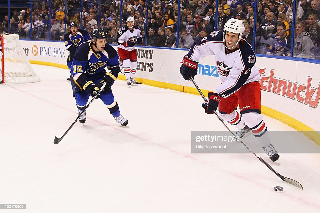 Derek MacKenzie of the Columbus Blue Jackets looks to pass the puck against Scott Nichol of the St Louis Blues at the Scottrade Center on February 23...