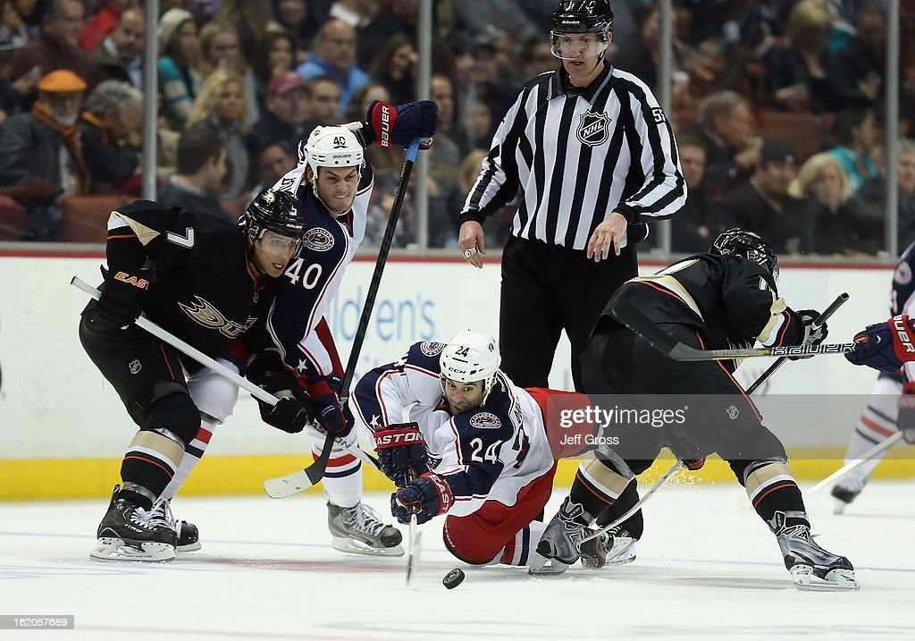 Derek MacKenzie #24 of the Columbus Blue Jackets lunges for the puck following a face-off, as Andrew Cogliano #7 of the Anaheim Ducks, Jared Boll #40 of the Columbus Blue Jackets and linesman Shane Heyer look on in the second period at Honda Center on February 18, 2013 in Anaheim, California. The Ducks defeated the Blue Jackets 3-2.