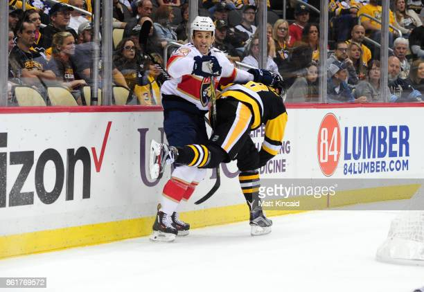 Derek MacKenzie of the Florida Panthers checks Brian Dumoulin of the Pittsburgh Penguins at PPG PAINTS Arena on October 14 2017 in Pittsburgh...
