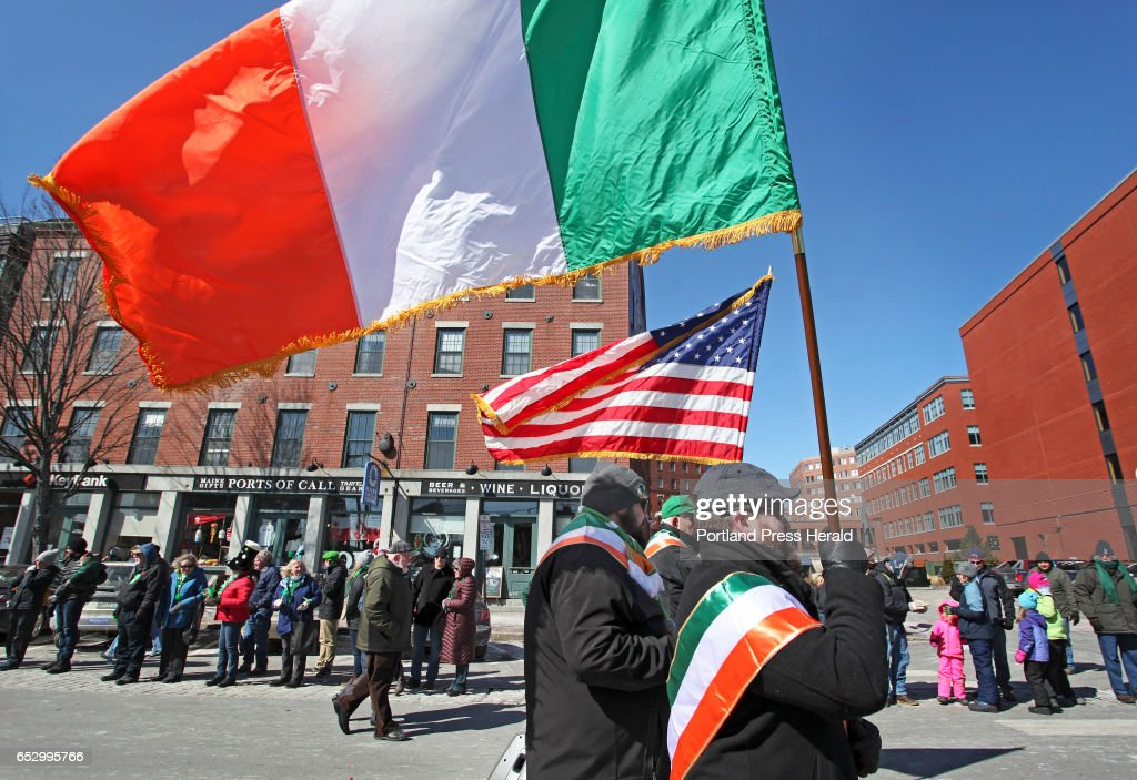 Derek McDonagh of Gorham, originally from Galway, and James McClay of Standish, originally from Donegal, carry the the Irish and American flags while walking with Division 1 of the Ancient Order of Hibernians in the Irish American Club's annual St. Patrick's Parade on Commercial Street.