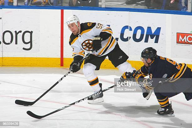 Derek Morris of the Boston Bruins handles the puck against Derek Roy of the Buffalo Sabres at HSBC Arena on January 29 2010 in Buffalo New York