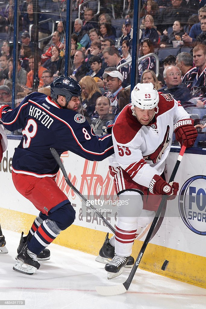 Derek Morris #53 of the Phoenix Coyotes attempts to skate the puck away from Nathan Horton #8 of the Columbus Blue Jackets during the first period on April 8, 2014 at Nationwide Arena in Columbus, Ohio.