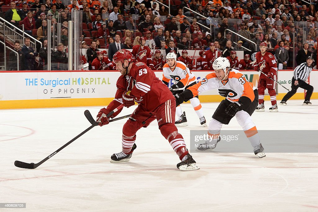 Derek Morris of the Phoenix Coyotes skates with the puck while being defended by Jay Rosehill of the Philadelphia Flyers at Jobingcom Arena on...
