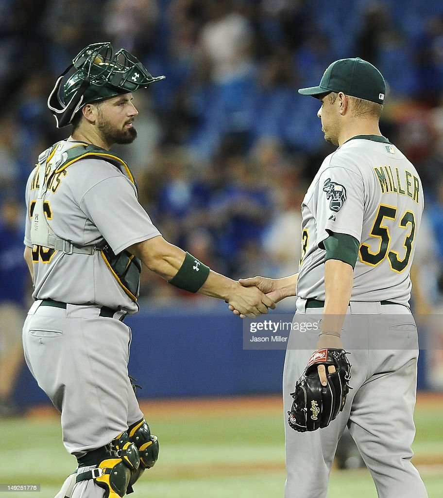 Derek Norris #36 and Jim Miller #53 of the Oakland Athletics celebrate the team's win over the Toronto Blue Jays during MLB game action July 25, 2012 at Rogers Centre in Toronto, Ontario, Canada.