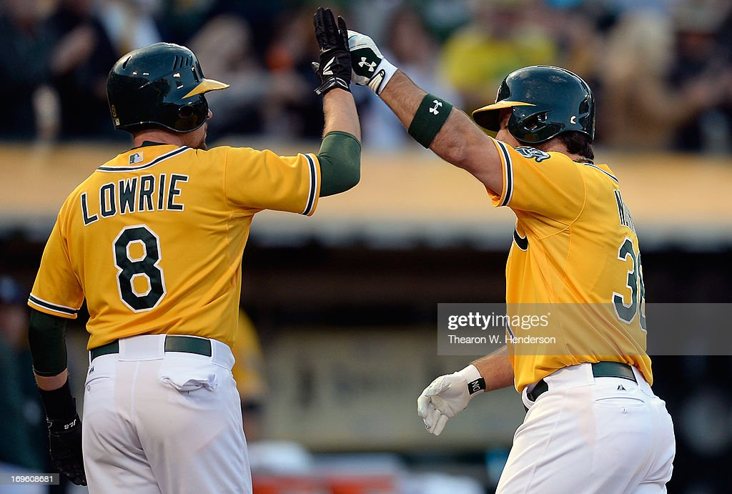 Derek Norris #36 of the Oakland Athletics is congratulated by Jed Lowrie #8 after Norris hit a two-run homer during the second inning against the San Francisco Giants at O.co Coliseum on May 28, 2013 in Oakland, California.