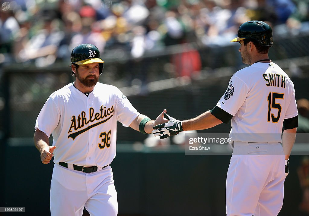 Derek Norris #36 of the Oakland Athletics is congratulated by Seth Smith #15 after he scored on a hit by John Jaso #5 in the first inning of their game against the Houston Astros at O.co Coliseum on April 17, 2013 in Oakland, California.