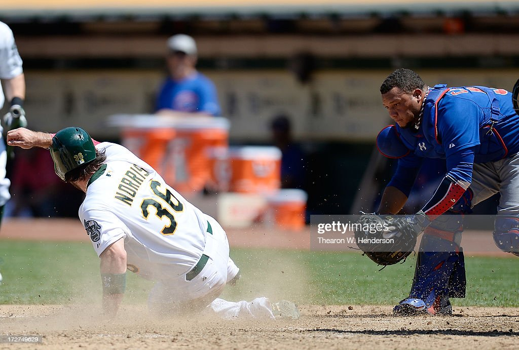 <a gi-track='captionPersonalityLinkClicked' href=/galleries/search?phrase=Derek+Norris&family=editorial&specificpeople=6795804 ng-click='$event.stopPropagation()'>Derek Norris</a> #36 of the Oakland Athletics scores on a past ball by catcher <a gi-track='captionPersonalityLinkClicked' href=/galleries/search?phrase=Welington+Castillo&family=editorial&specificpeople=4959193 ng-click='$event.stopPropagation()'>Welington Castillo</a> #53 of the Chicago Cubs in the seventh inning at O.co Coliseum on July 4, 2013 in Oakland, California.