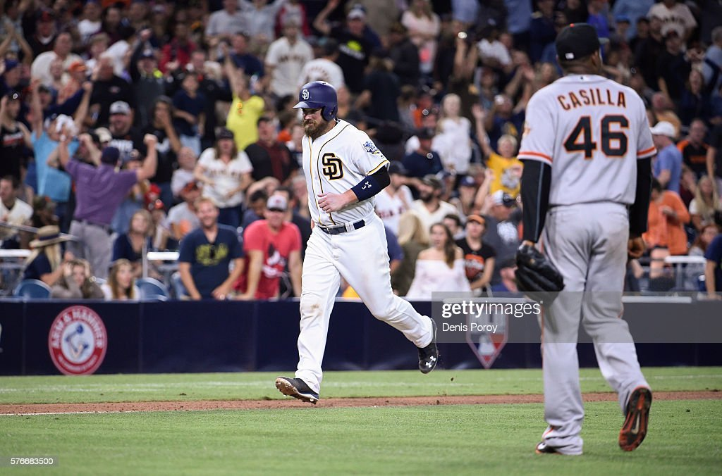 Derek Norris of the San Diego Padres scores on a balk as Santiago Casilla of the San Francisco Giants walks off the field during the tenth inning of...