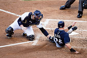 Derek Norris of the San Diego Padres tags Michael Reed of the Milwaukee Brewers out at the plate during the third inning of a baseball game at Petco...