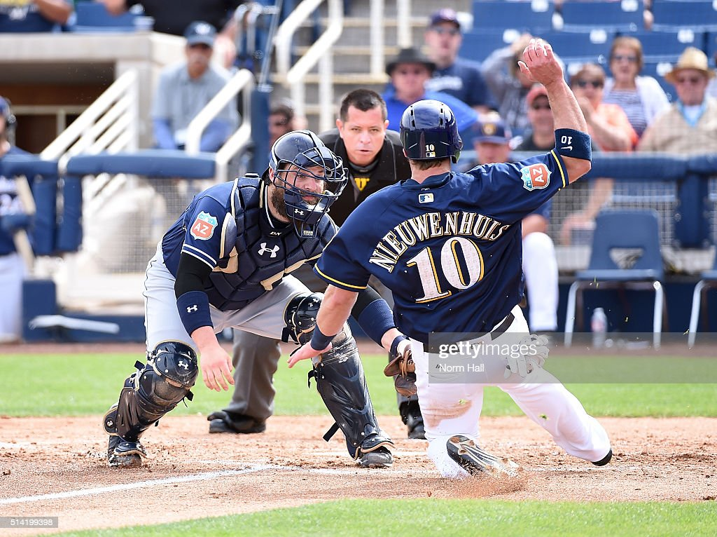 Derek Norris of the San Diego Padres tags out Kirk Nieuwenhuis of the Milwaukee Brewers at home plate during the second inning of a spring training...