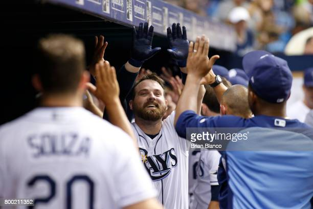 Derek Norris of the Tampa Bay Rays celebrates in the dugout with teammates after hitting a tworun home run off of pitcher Ubaldo Jimenez of the...