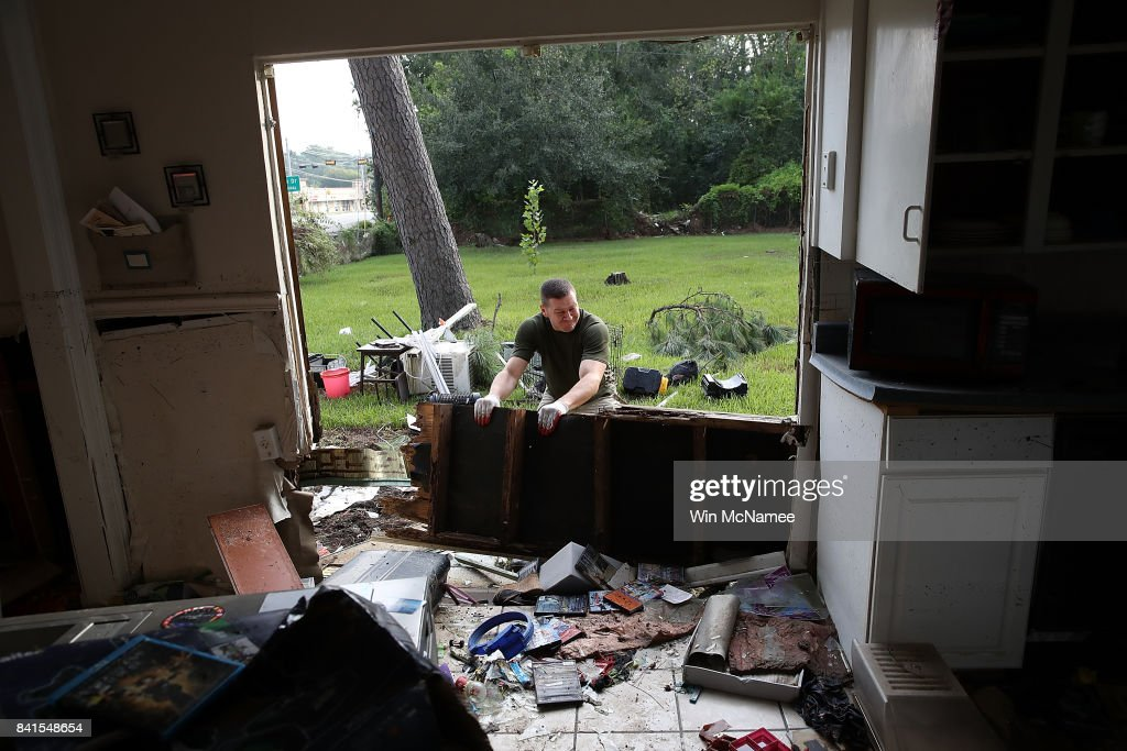 Derek Pelt removes a portion of his friend Bryan Parson's home while helping to remove damage caused by flooding brought on by Hurricane Harvey September 1, 2017 in Dickinson, Texas. Dickinson was hit by Hurricane Harvey extremely hard with major flooding in many areas of the city and residents there are beginning the long process of recovery from the storm.