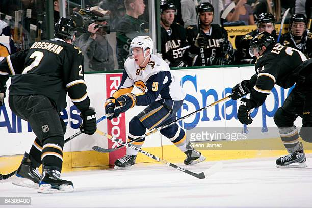 Derek Roy of the Buffalo Sabres handles the puck against Nicklas Grossman and Loui Eriksson of the Dallas Stars at the American Airlines Center...