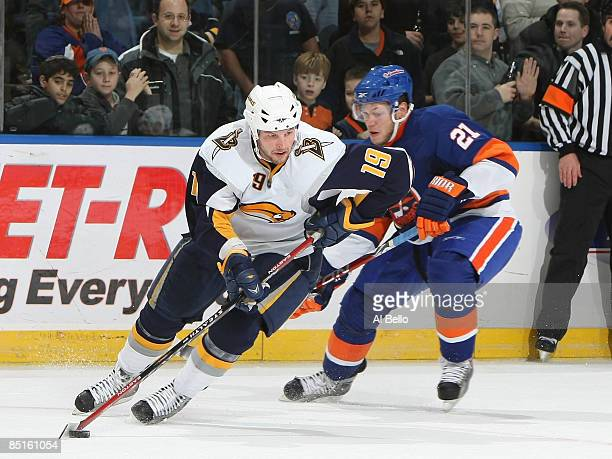 Derek Roy of the Buffalo Sabres handles the puck as Kyle Okposo of the New York Islanders defends during their game at the Nassau Coliseum on...
