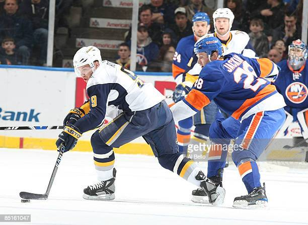 Derek Roy of the Buffalo Sabres handles the puck as Tim Jackman of the New York Islanders defends during their game at the Nassau Coliseum on...