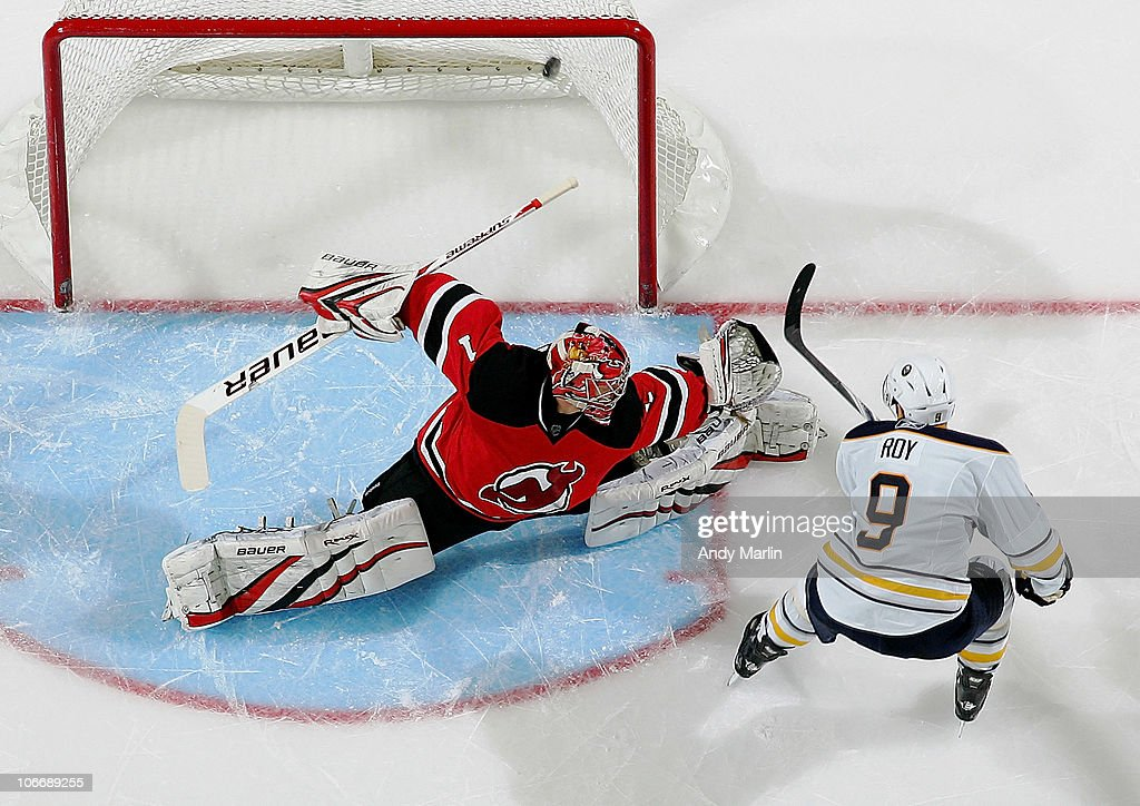 Derek Roy of the Buffalo Sabres puts the puck into the top right corner of the net against goaltender Johan Hedberg of the New Jersey Devils for the...