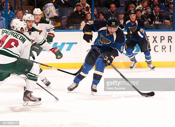 Derek Roy of the St Louis Blues handles the puck as Jared Spurgeon of the Minnesota Wild defends on November 25 2013 at Scottrade Center in St Louis...