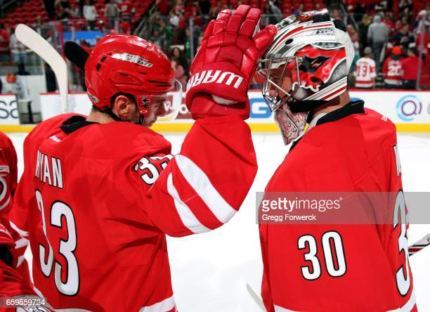 Derek Ryan and Cam Ward of the Carolina Hurricanes celebrate their team's 41 victory over the Detroit Red Wings following an NHL game on March 28...