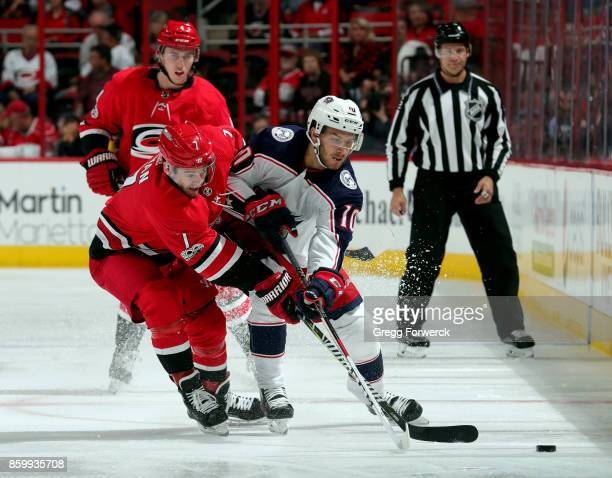Derek Ryan of the Carolina Hurricanes and Alexander Wennberg of the Columbus Blue Jackets struggle for possession of the puck during an NHL game on...