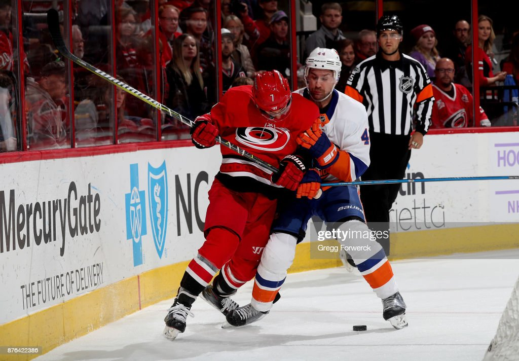 Derek Ryan #7 of the Carolina Hurricanes and Calvin de Haan #44 of the New York Islanders battle along the boards for possession during an NHL game on November 19, 2017 at PNC Arena in Raleigh, North Carolina.