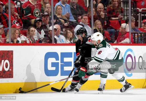 Derek Ryan of the Carolina Hurricanes and Marco Scandella of the Minnesota Wild battle for the loose puck along the boards during an NHL game on...