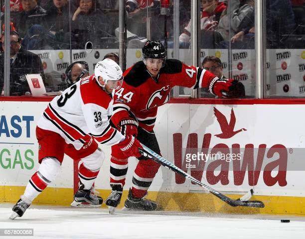 Derek Ryan of the Carolina Hurricanes and Miles Wood of the New Jersey Devils fight for the puck in the third period on March 25 2017 at Prudential...