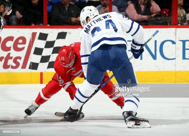 Derek Ryan of the Carolina Hurricanes faces off against Auston Matthews of the Toronto Maple Leafs during an NHL game on March 11 2017 at PNC Arena...