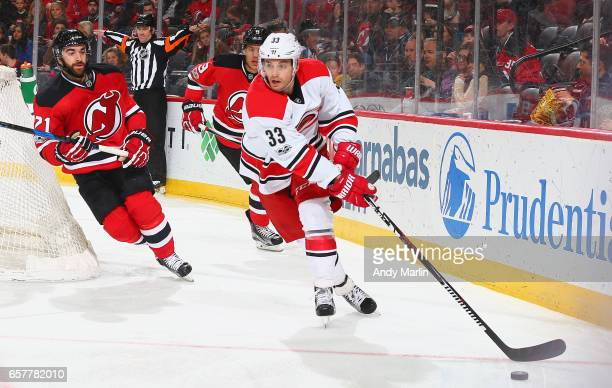 Derek Ryan of the Carolina Hurricanes plays the puck while being pursued by Kyle Palmieri during the game at Prudential Center on March 25 2017 in...