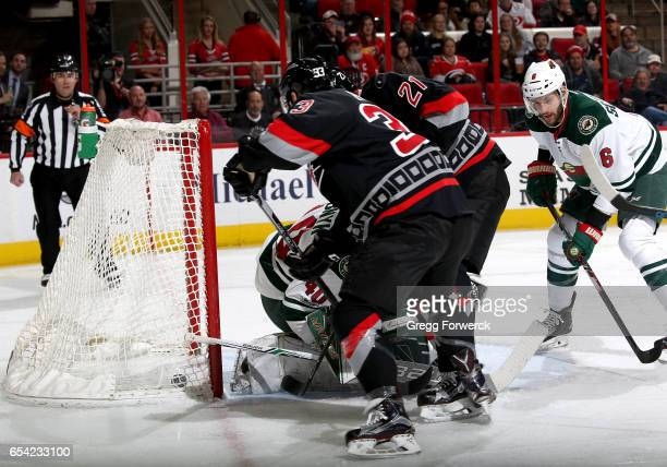 Derek Ryan of the Carolina Hurricanes scores past the defense of goaltender Devan Dubnyk of the Minnesota Wild during an NHL game on March 16 2017 at...