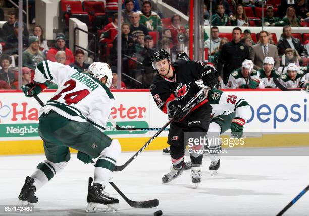 Derek Ryan of the Carolina Hurricanes shoots the puck past the defense of Matt Dumba of the Minnesota Wild during an NHL game on March 16 2017 at PNC...