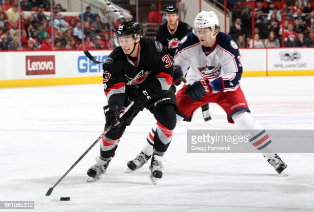 Derek Ryan of the Carolina Hurricanes skates the puck ahead of Josh Anderson of the Columbus Blue Jackets during an NHL game on March 30 2017 at PNC...