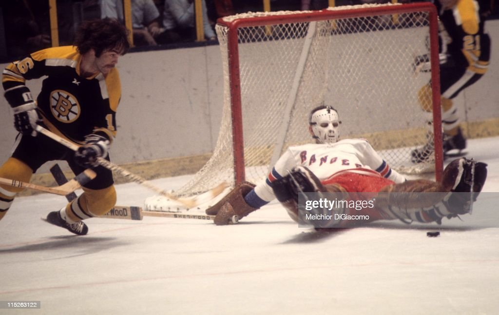 Derek Sanderson of the Boston Bruins looks to score as goalie Ed Giacomin of the New York Rangers tries to make the save during their game circa 1972...