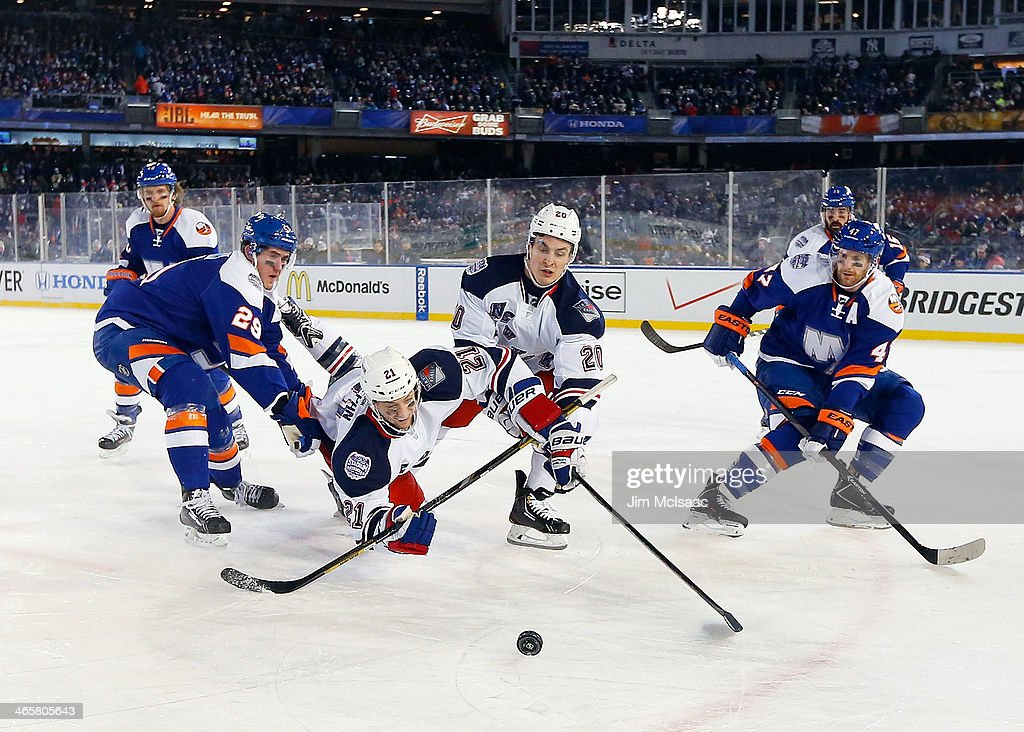 Derek Stepan and Chris Kreider of the New York Rangers battle for the puck against Brock Nelson and Andrew MacDonald of the New York Islanders during...