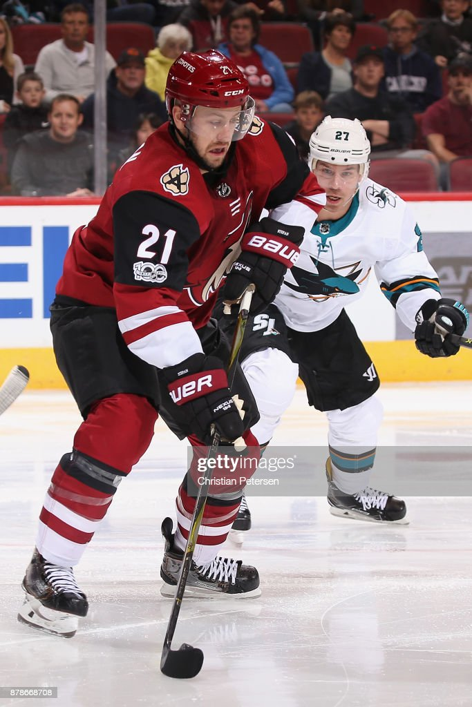 Derek Stepan #21 of the Arizona Coyotes controls the puck ahead of Joonas Donskoi #27 of the San Jose Sharks during the third period of the NHL game at Gila River Arena on November 22, 2017 in Glendale, Arizona. The Sharks defeated the Coyotes 3-1.